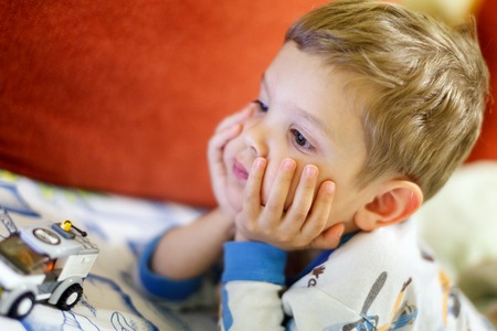 watching movie: Boy lying on bed watching movie or cartoon on pad. Screen enlighten his face