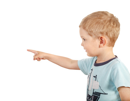 towards: The boy points his finger towards. Halflength portrait arms down. White background Stock Photo