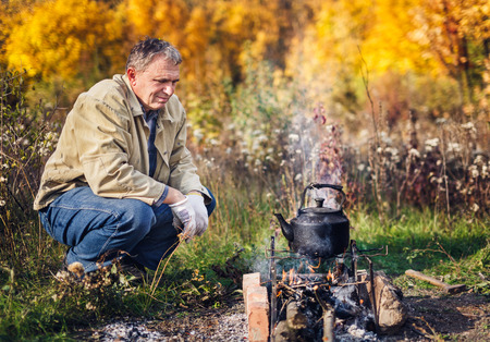 sooty: man boils sooty kettle on the campfire, autumn Stock Photo