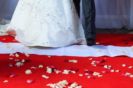 congratulating: Congratulating wife for wedding. Wedding guests toasting happy bride. Selective focus on floor with rose petals. Moments of wedding ceremony
