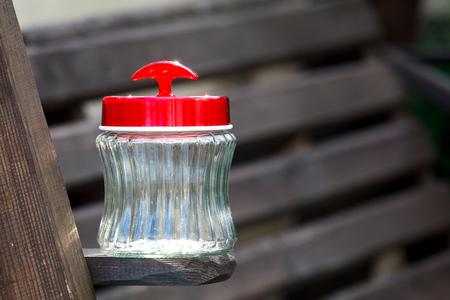 empty jar: Empty jar whith red plastic cover on a  wooden board