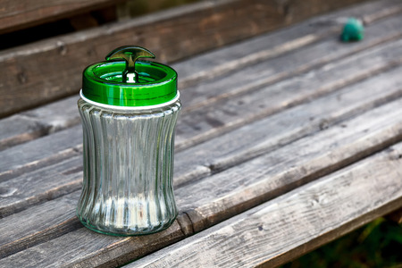 empty jar: Empty jar with green plastic cover on a  wooden board