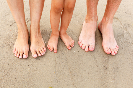 wet men: Family feet in the sand on the beach Stock Photo