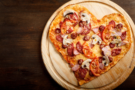 crust: Pizza heart shape on dark wooden background top view. Thin pastry crust on wooden desk