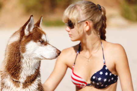 beach blond hair: Young girl sits on the beach with the husky dog