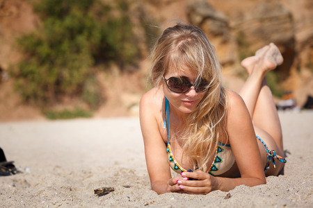 sexy boobs: young blonde woman lying on the sand on the beach Stock Photo