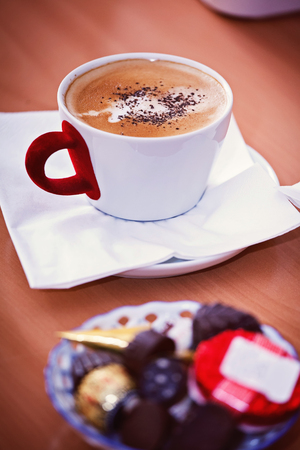 a view of a cup of cappaccino with chocolates in the background