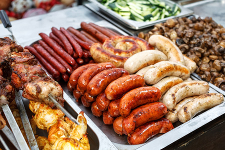 chitterlings: Assorted German sausages grilled in a steel container. Street food market