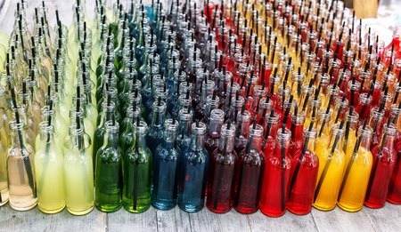 Colorful cocktails, shots with straws in small glass bottles. Row of many lemonade drinks