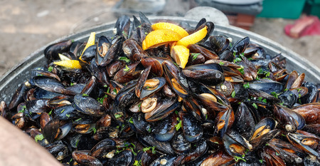 Steamed black sea mussels in cream sauce with carrot Stock Photo