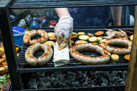 chitterlings: Grilling assorted sausages and quail on the market showcase