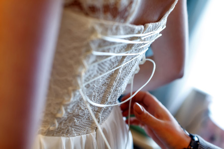 mother lace corset her daughter for the wedding ceremony. Stock Photo