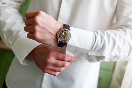 A man arranging his buttonholes on a background of a white shirt, sleeve shirt and watches, photographed close-up