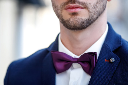 bearded man in a blue jacket and a bow tie