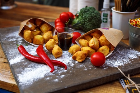 Breaded potato croquettes with tomato on a wooden table close-up Stock Photo