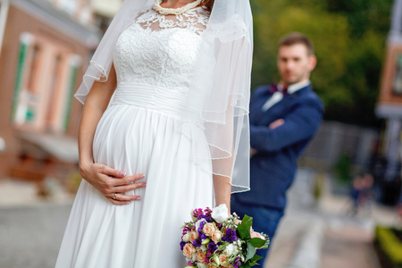 Pregnant bride in a wedding gown holding belly with hands. the groom in a tuxedo in the background Stock Photo
