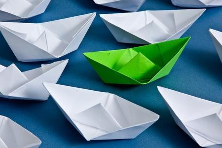 White paper boats and one green boat
