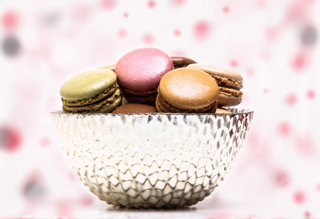colored background: Colored macarons inside bowl on colored background Stock Photo