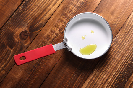 Fry pan with oil on wooden background Banco de Imagens