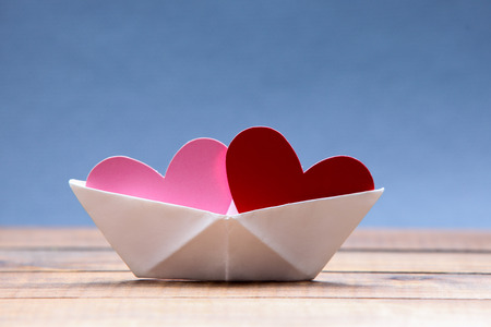 Paper hearts inside paper boat with blue background