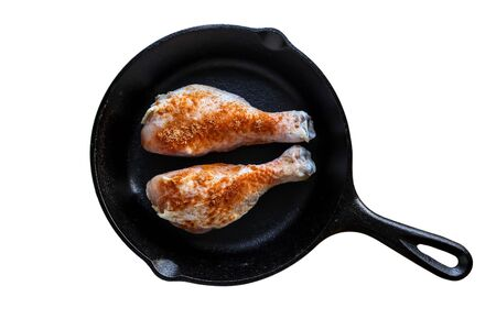 Iron skillet with chicken leggs and seasoning isolated on white 写真素材
