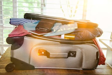 Full suitcase packed for vacation without more space and sunbeams from window