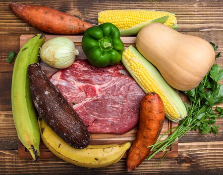 Vegetables and meat on wooden background for beef stew