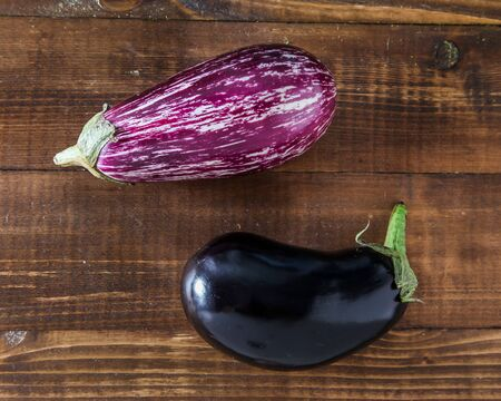 Two little eggplants on wooden background