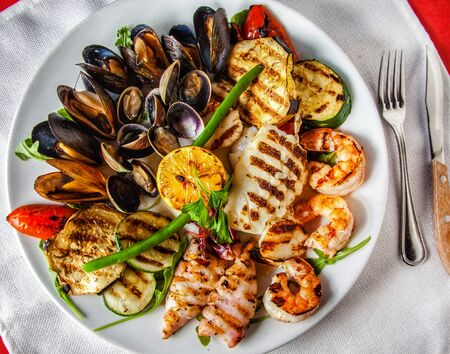 Grilled seafood dish on white plate