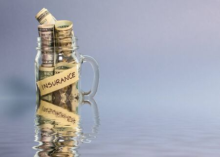 Money for flood insurance in jar with