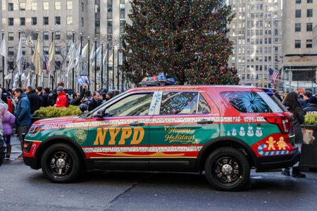 NEW YORK, NY, USA - DECEMBER 27, 2018: NYPD car with happy holidays wish near christmas tree at Rockefeller Center