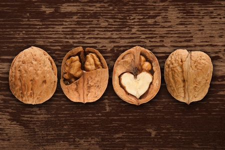 walnuts on brown wooden background, the whole and crashed