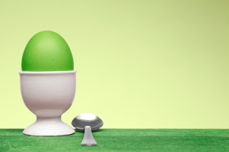 eggcup: green egg in white cup on blank background