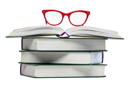 red glasses on open book, pile or stack of books isolated over white background photo