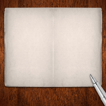 open blank pages book with silver fountain pen on brown wooden background photo