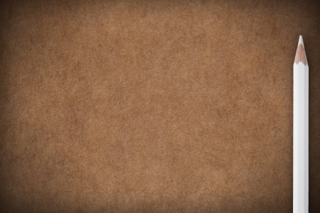brown paper background with white crayon on right side and empty place for text photo