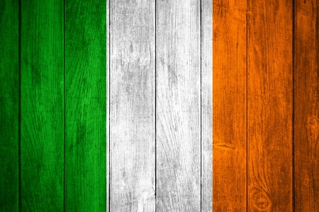 Ireland flag or green, white and  orange Irish banner on wooden background photo