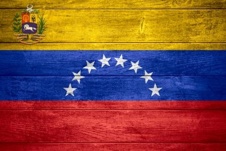 flag of Venezuela or  Venezuelan banner on wooden background photo