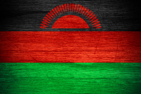 malawi flag: Malawi flag or banner on wooden texture