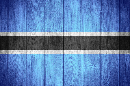 botswanan: Botswana flag or Botswanan banner on wooden boards background Stock Photo
