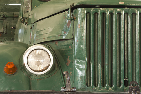reflector: front of old green lorry with grille and reflector