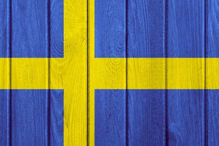 swedish: flag of Sweden or Swedish banner on wooden background Stock Photo
