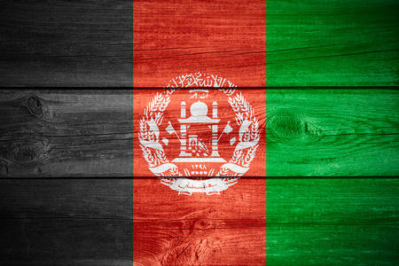 afghan flag: flag of Afghanistan or Afghan banner on wooden background