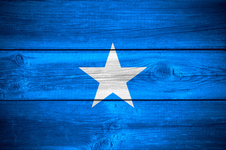 somalian: flag of Somalia or Somalian banner on wooden background Stock Photo