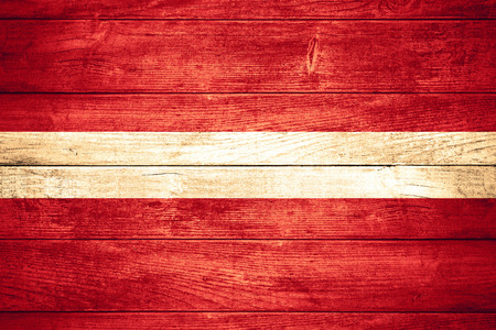 flag of Latvia or Latvian banner on wooden background