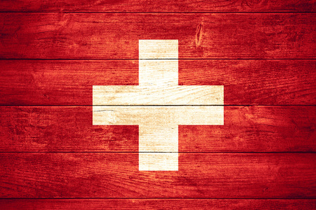 swiss culture: flag of Switzerland or Swiss banner on wooden background