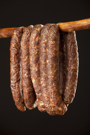 hanging smoked sausage on a stick on black background