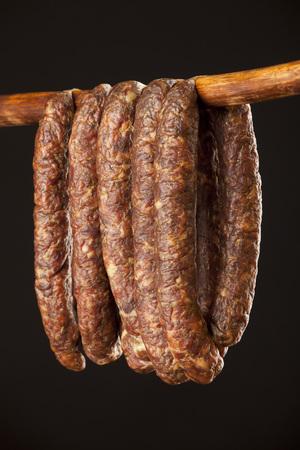 dry sausage: hanging smoked sausage on a stick on black background Stock Photo