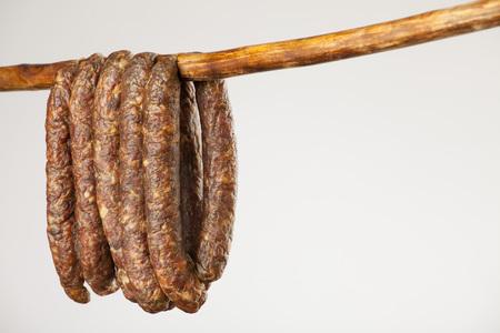 dry sausage: hanging smoked sausage on a stick on white background Stock Photo