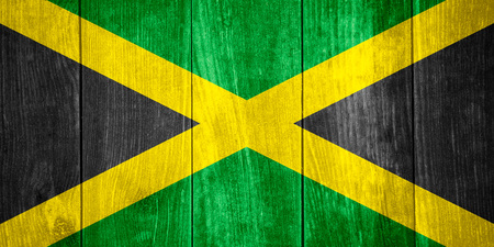 flag of Jamaica or Jamaican banner on wooden background